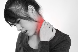 Young woman holding neck in pain and discomfort