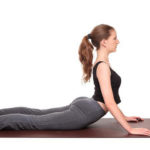 Isolated studio shot of a fit Caucasian woman holding the bhujangasana Cobra Pose yoga position on an exercise mat.