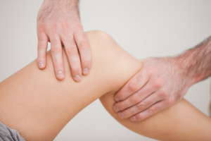 @Glowimages: Knee of a patient being touched by a practitioner in a room. Knee of a patient being touched by a practitioner